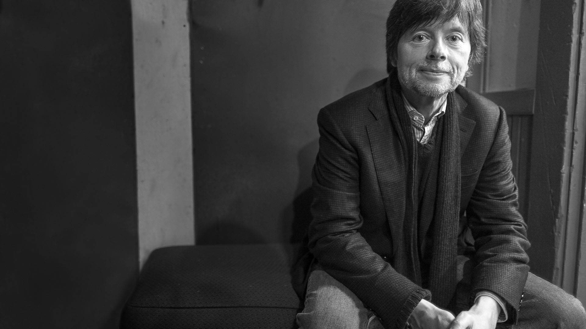 A black-and-white photo of Ken Burns seated, looking at the camera.