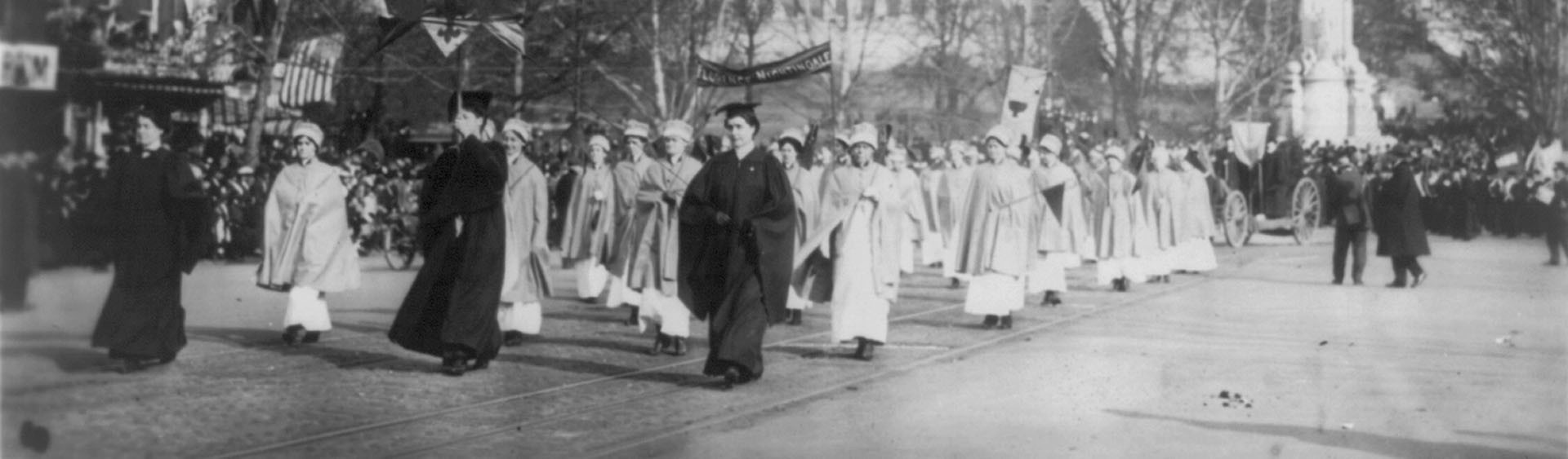 A black-and-white image with has been split into two pieces horiontally. This is the second piece. The image depicts a procession of female nurses in 1913, in Washington D.C., as they hold banners aloft which proclaim support of the suffragettes.