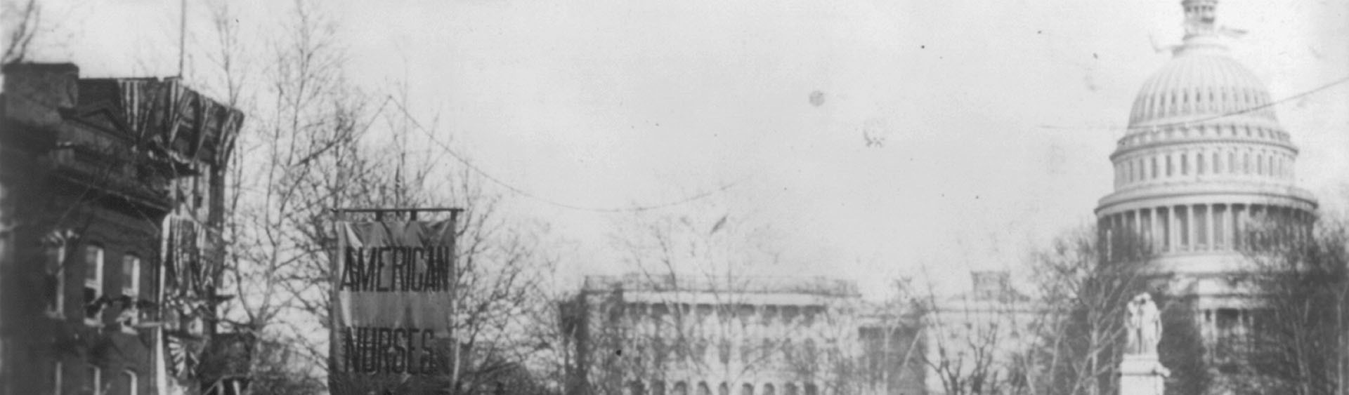 A black-and-white image with has been split into two pieces horiontally. This is the first piece. The image depicts a procession of female nurses in 1913, in Washington D.C., as they hold banners aloft which proclaim support of the suffragettes.