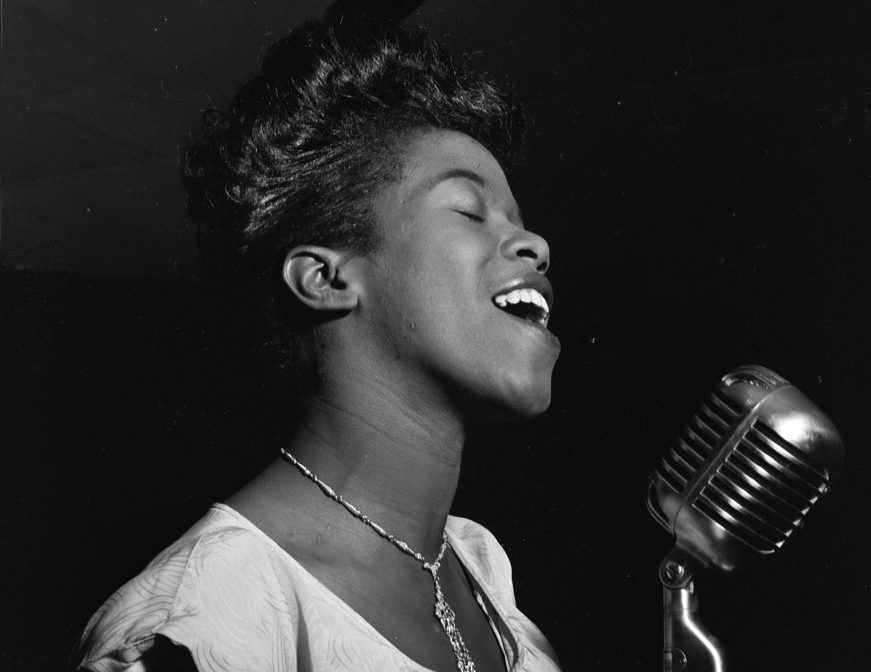 A black and white photo of Sarah Vaughan singing into a microphone, possibly at Cafe Society, NYC, ca. August 1946.