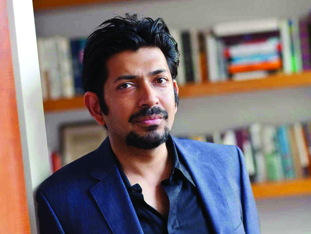 Photograph of Dr. Siddhartha Mukherjee with a bookshelf in the background.