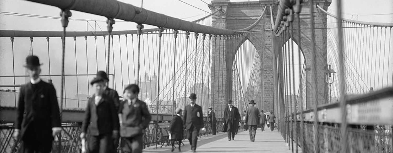 A black-and-white photo of people crossing the Brooklyn Bridge in the early 20th century.
