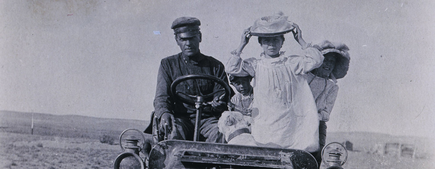 A black-and-white photo of a family sitting in an old-fashioned, open-air car. Horatio Nelson Jackson is sitting in the driver's seat, alongside his wife. Two children are peeking out from behind the woman's back, and a dog is seated, turned away from the camera, in the front.