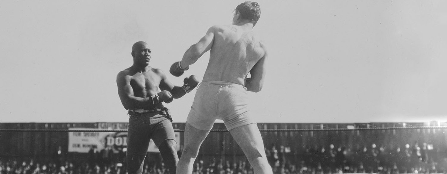 A black-and-white photo of Jack Johnson in a wrestling ring, fighting an opponent. Johnson's opponent has his back to the camera and Johnson is squaring up against him, facing the camera. There are many people in the crowd.
