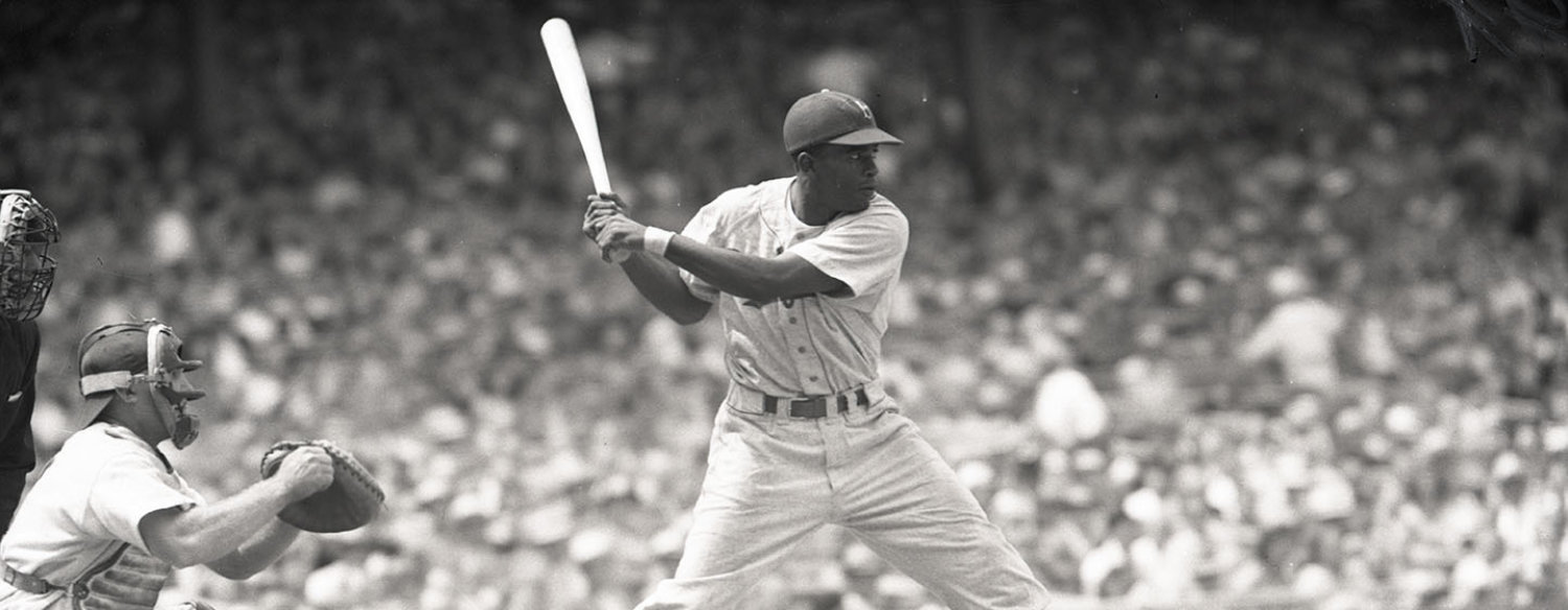 A black-and-white photo of Jackie Robinson batting during a baseball game. He is mid-swing.