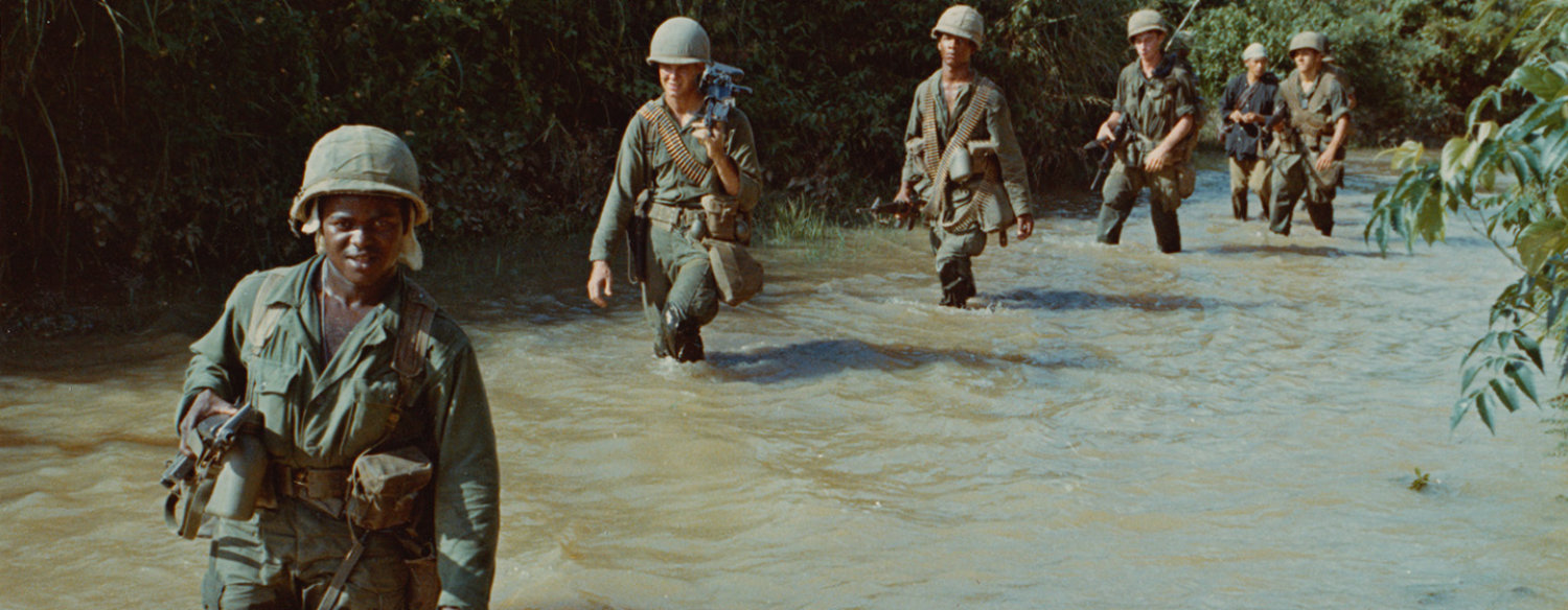A color photo of Vietnam-era American military personnel trudging through thigh-deep water, in a single-file line, in the Vietnamese jungle.