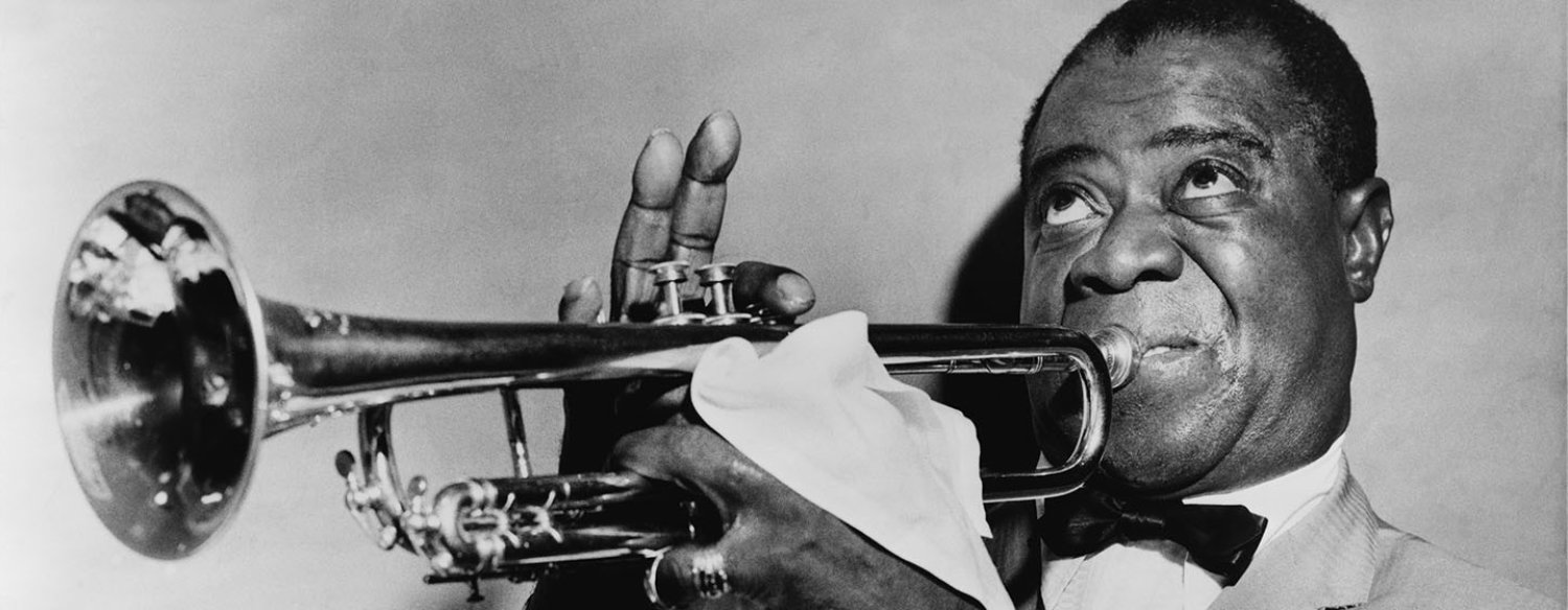 A black-and-white photo of Louis Armstrong playing the trumpet, taken in 1953.