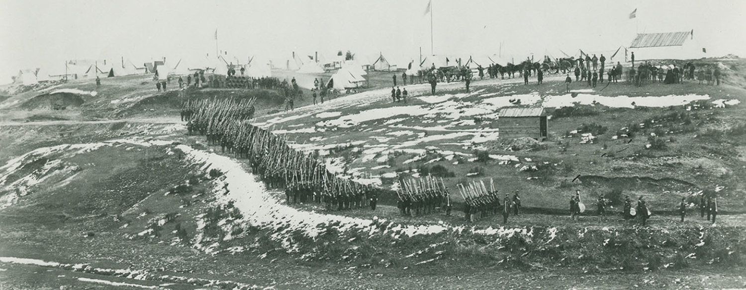 A black-and-white photo showing Union troops conducting drills on snow-blanketed hills near Washington, D.C., circa 1861–65.