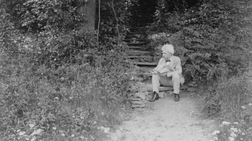 A black-and-white photo of Mark Twain sitting on outdoor steps along a secluded garden path, surrounded by greenery. He is looking away from the camera.   Timeline