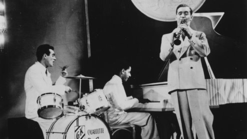 Black-and-white photos showing The Benny Goodman Trio performing, with Benny Goodman on the trumpet, Gene Krupa on the drums, and Teddy Wilson on the piano, in 1937. | Music 101