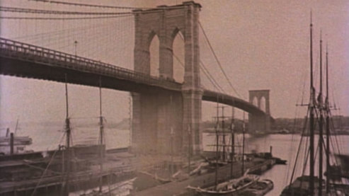 A sepia-toned photo of the Brooklyn Bridge, taken from below. Boats are moored in the foreground. | Ken Burns and Jim Dwyer in Conversation