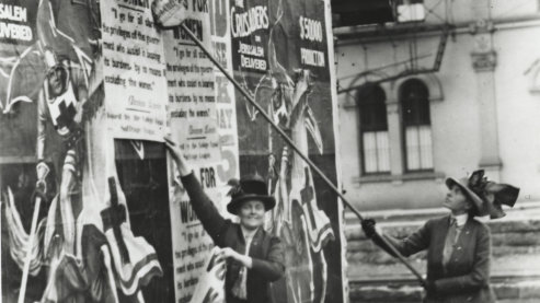 A black-and-white photo that shows two women in early twentieth century garb plastering posters on a wall which call for women's right to vote. | Women's Suffrage