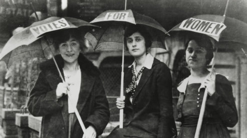 """A black-and-white photo of three women looking at the camera as they carry open umbrellas. Each umbrella has one word on it which spells out """"Votes For Women."""" 