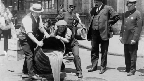 New York City Deputy Police Commissioner John A. Leach, right, watching agents pour liquor into sewer following a raid, ca. 1921. After the Mullan-Gage Act was repealed in 1923, New York police were no longer bound to enforce Prohibition. | Video