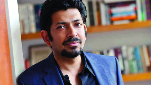 Photograph of Dr. Siddhartha Mukherjee with a bookshelf in the background.   About the Film