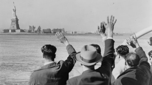 A black-and-white photo of a group of men waving goodbye to the Statue of Liberty in the distance, as their boat sails away. | Timeline