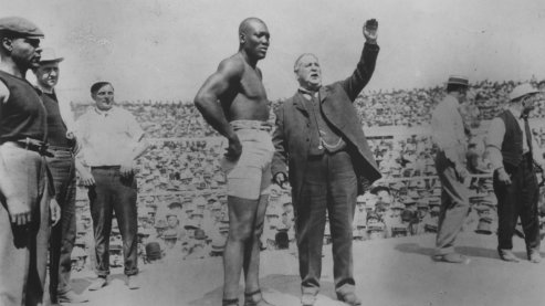 A black-and-white photo of Jack Johnson in a boxing ring, standing next to an announcer, as other men also stand nearby. The announcer has his hand raised above his head. | Timeline