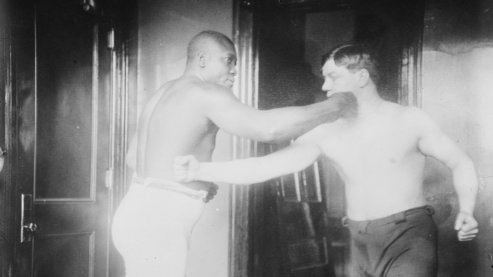 A black-and-white photo of Jack Johnson posing with another boxer. They are both pantomiming punching one another. The other boxer's fist is connecting with Johnson's chest while Johnson is connecting with his opponent's jaw. | Boxing Glossary
