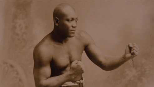 A sepia-toned photo of Jack Johnson posing in a boxing stance. | Video