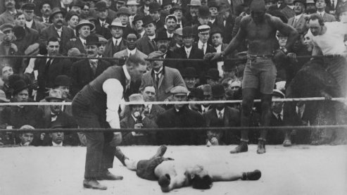 A black-and-white photo of Jack Johnson standing in a boxing ring, over a prone, defeated opponent. The umpire is counting the opponent out and there is a large crowd in the background. | About Jack Johnson