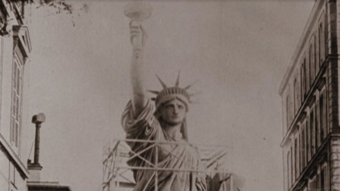 A sepia toned photo of the Statue of Liberty's upper half, partially surrounded by scaffolding. | The Idea