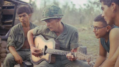 """A color photo of an American serviceman playing an acoustic guitar as several other military members gather around to listen. The man playing the guitar wears a camouflage helmet with the words """"Oklahoma Kid"""" scrawled on it.   Music"""