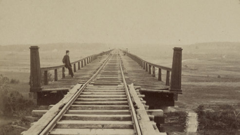 A sepia-toned photo of a railway bridge stretching away from the camera, into the distance. A lone man in civil-war-era clothing leans against the wooden railing. | Timeline