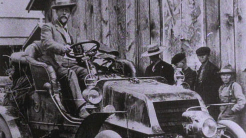 A lilac-hued photo of a man sitting atop an old-fashioned, open-air vehicle. He is dressed in formal attire. There are a line of people standing nearby wearing more simple clothing. | Ken Burns on Horatio's Drive