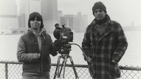 A black-and-white photo taken in the 1980s depicting Ken Burns standing next to another man and a camera on a tripod. | A Note from Ken Burns