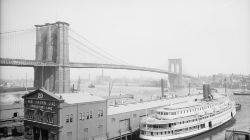 A black-and-white photo taken in the early 20th century, depicting the Brooklyn Bridge with a large ferry in the foreground. | Timeline