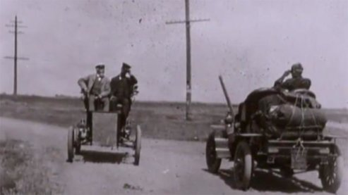 A lilac-hued photo of two old-fashioned cars passing one another. The drivers are tipping their caps to each other. | Video